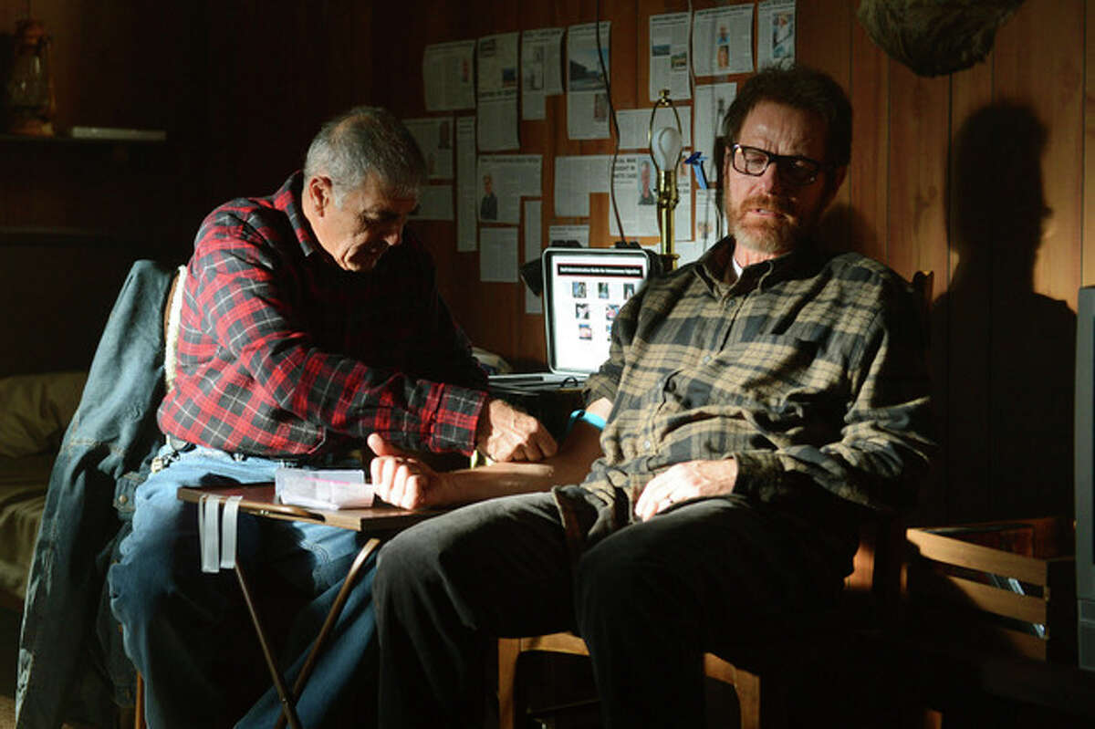 This image released by AMC shows Ed, a fixer portrayed by Robert Forster, administering medicine to Walter White, played by Bryan Cranston in a scene from the final season of