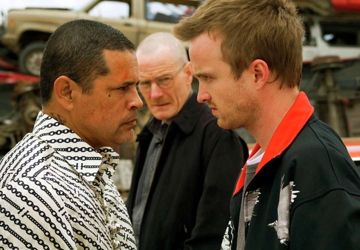 This image released by AMC shows drug dealer Tuco Salamanca, played by Raymond Cruz, left, staring down Jesse Pinkman, played by Aaron Paul, right, as Walter White, played by Bryan Cranston, looks on during the second season of