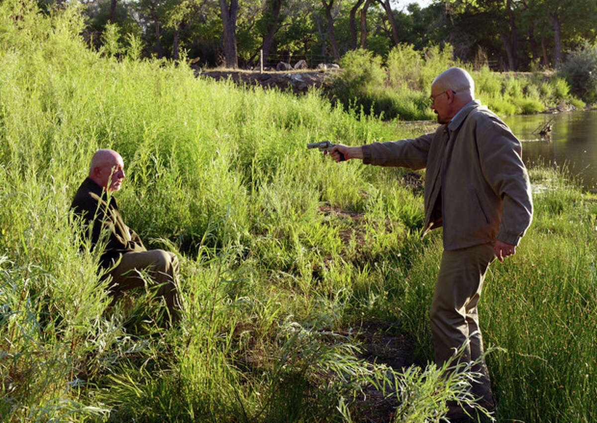 """This Image released by AMC shows Walter White played by Bryan Cranston, right, pointing a gun at Mike Ehrmantraut, played by Jonathan Banks in a scene from the fifth season of """"Breaking Bad."""" The series finale of the popular drama series airs on Sunday, Sept. 29. (AP Photo/AMC, Ursula Coyote)"""