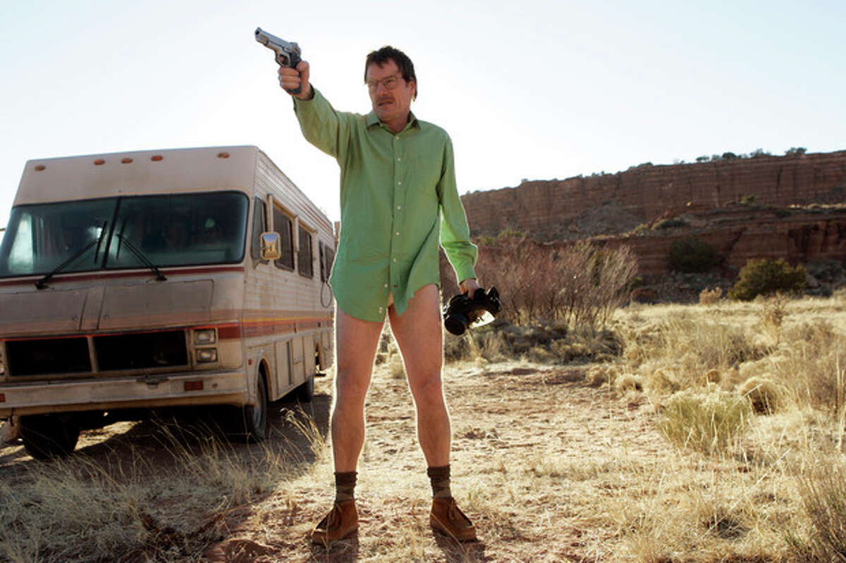 """This image released by AMC shows Walter White, played by Bryan Cranston, next to the Winnebago he uses as a mobile meth lab in the pilot episode of """"Breaking Bad."""" The series finale of the popular drama series airs on Sunday, Sept. 29. (AP Photo/AMC, Doug Hyun)"""