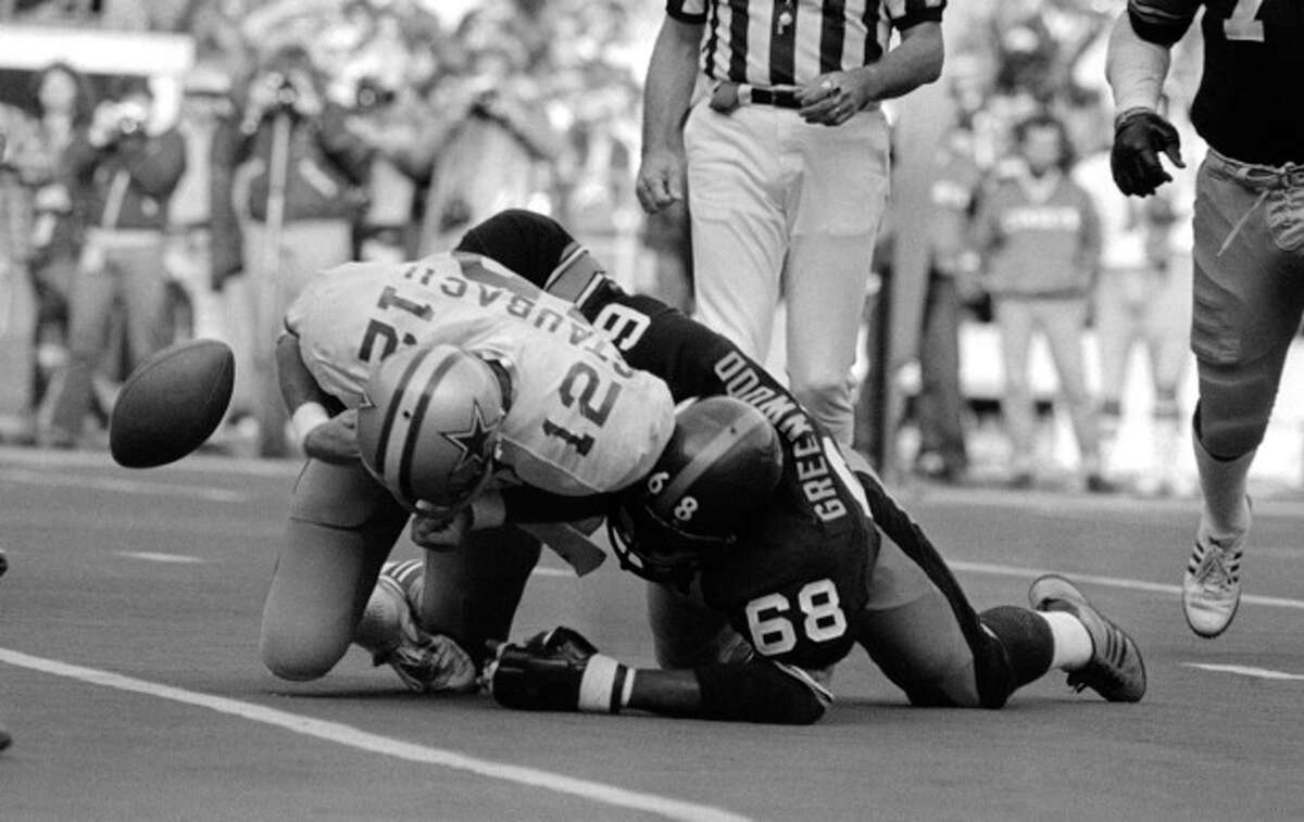 FILE - In this Oct. 28, 1979 file photo, the ball pops loose as Dallas quarterback Roger Staubach is tackled by Pittsburgh Steelers' L.C. Greenwood during a football game in Pittsburgh. Greenwood, who won four Super Bowls as a member of the