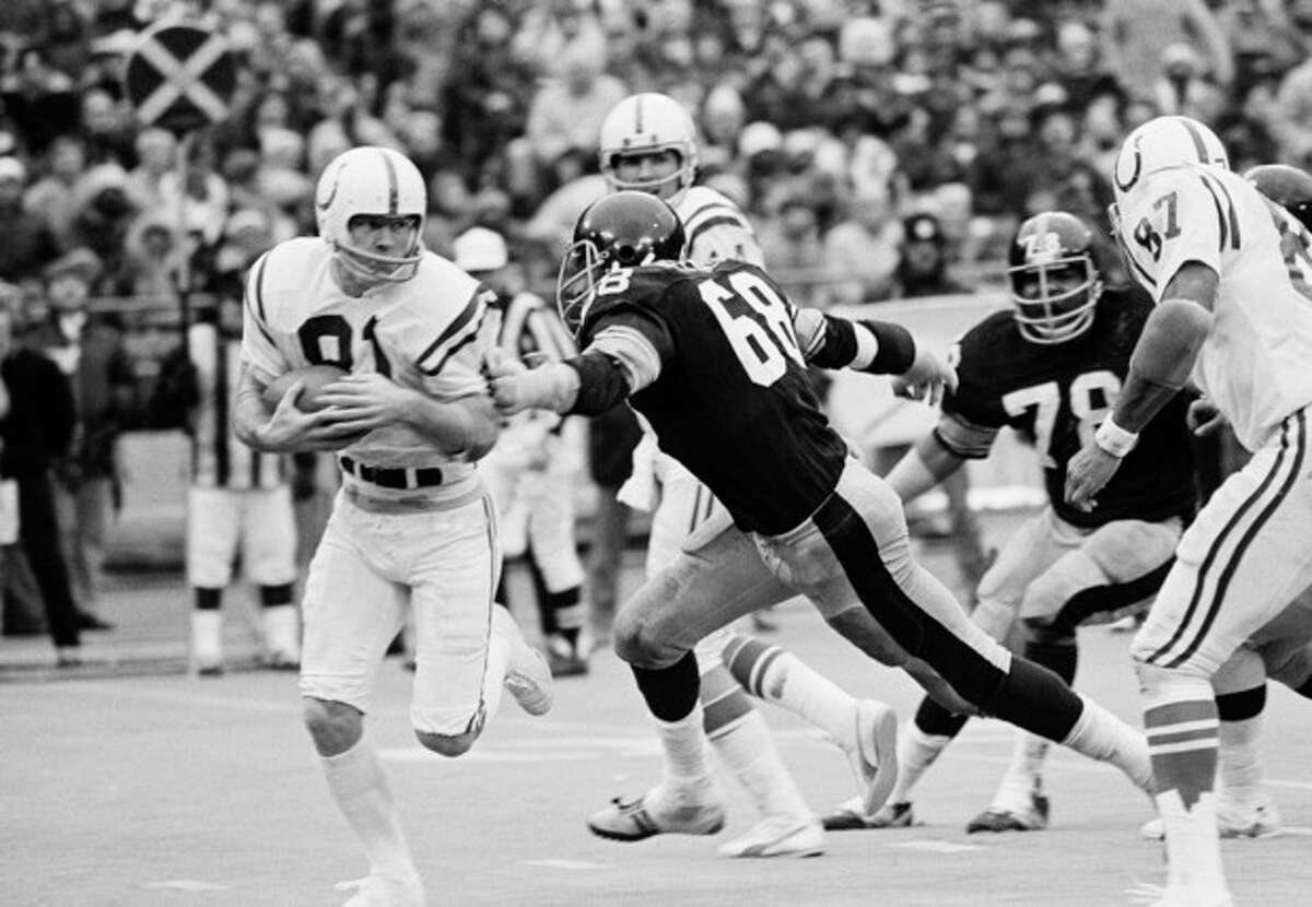 FILE - in this Dec. 27, 1975 file photo, Baltimore Colts wide receiver Roger Carr scampers past Pittsburgh Steelers defensive end L.C. Greenwood (68) during a football game in Pittsburgh. Greenwood, who won four Super Bowls as a member of the