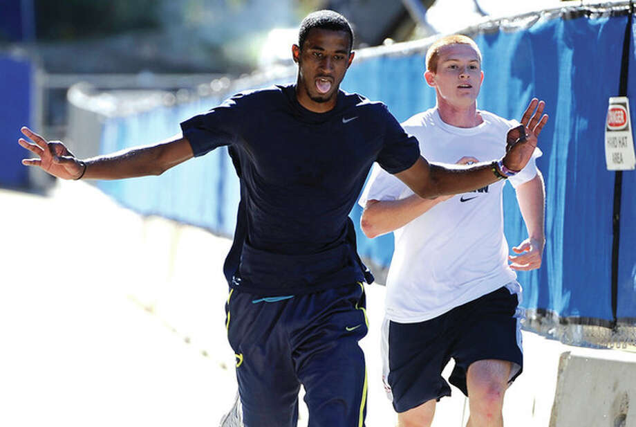 AP photoDeAndre Daniels, left, edges teammate Pat Lenehan to be the first player to finish the 3.4-mile Husky Run Wednesday in Storrs. The annual run marks the start of the season for the UConn men's basketball team. / FR125654 AP