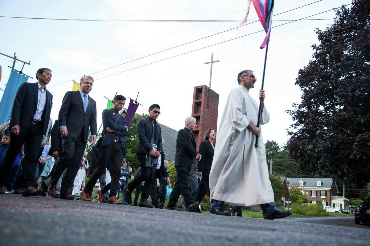 A procession walks from St. Mark's Cathedral to St. James Cathedral in solidarity and hope following the shooting at a club in Orlando, Florida, on Wednesday, June 15, 2016.