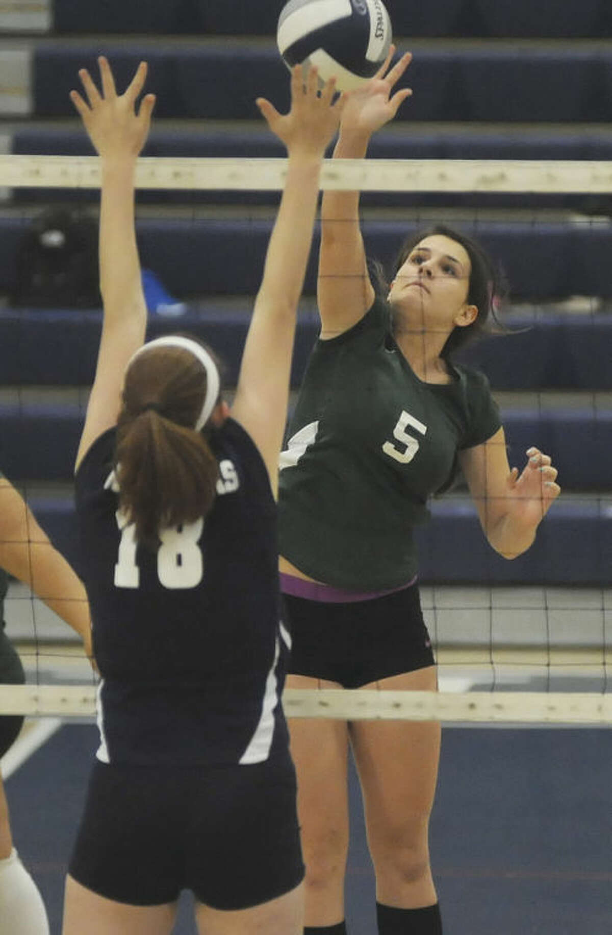 Hour photo/John Nash Norwalk's Alex Weber (5) sends down a shot against the defense of Wilton's Natalie Smith during Monday's FCIAC volleyball game at the Zeoli Field House in Wilton. Norwalk won the match 3-1.