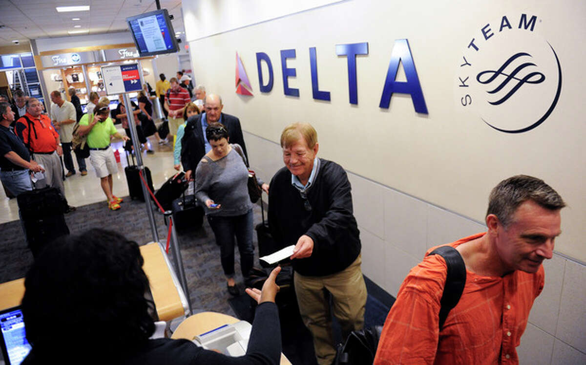 In this Friday, Sept. 27, 2013, photo, Delta Air Lines passengers, who have purchased an upgrade to board their flight early, take advantage of priority boarding as they make their way to their flight at Hartsfield-Jackson Atlanta International Airport in Atlanta. Airlines are introducing a new bevy of fees, but this time passengers might actually like them. Unlike the first generation of charges which dinged fliers for once-free services like checking a bag, these new fees promise a taste of the good life, or at least a more civil flight. In the near future, airlines plan to go one step further, using massive amounts of personal data to customize new offers for each flier. (AP Photo/John Amis)