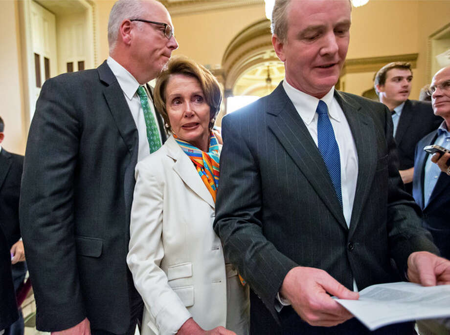 House Minority Leader Nancy Pelosi, D-Calif., center, squeezes between Rep. Joe Crowley, D-N.Y., left, and Rep. Chris Van Hollen, D-Md., right, as they return to negotiations following a news conference just before midnight at the Capitol in Washington, Monday, Sept. 30, 2013. For the first time in nearly two decades, the federal government staggered into a partial shutdown Monday at midnight after congressional Republicans stubbornly demanded changes in the nation's health care law as the price for essential federal funding and President Barack Obama and Democrats adamantly refused. (AP Photo/J. Scott Applewhite) / AP