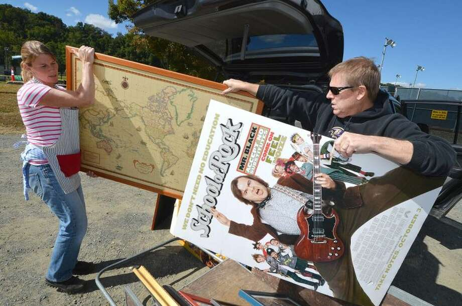 Hour Photo/Alex von Kleydorff Minks to Sinks Co Chair Trish Weber helps Bucky Guntz unload some framed artwork for donation and consignment for this weekends Minks to Sinks Sale to benefit family and Childrens Agency of Norwalk.