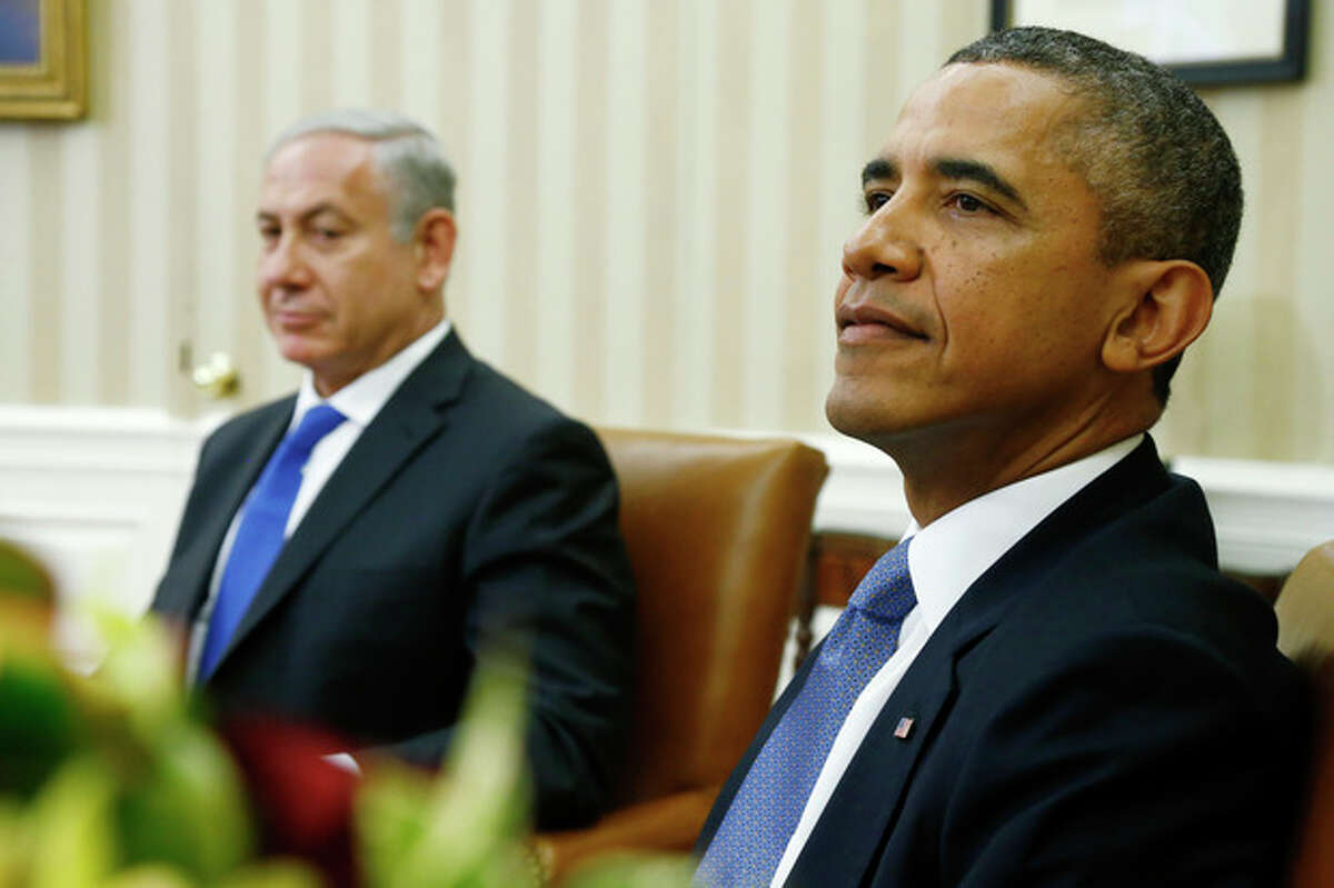 President Barack Obama and Israeli Prime Minister Benjamin Netanyahu wait for reporters and cameramen to get in place before they make statements in the Oval Office of the White House in Washington, Monday, Sept. 30, 2013. The White House said the two leaders would discuss negotiations with the Palestinians, developments in Syria and Iran. (AP Photo/Charles Dharapak)
