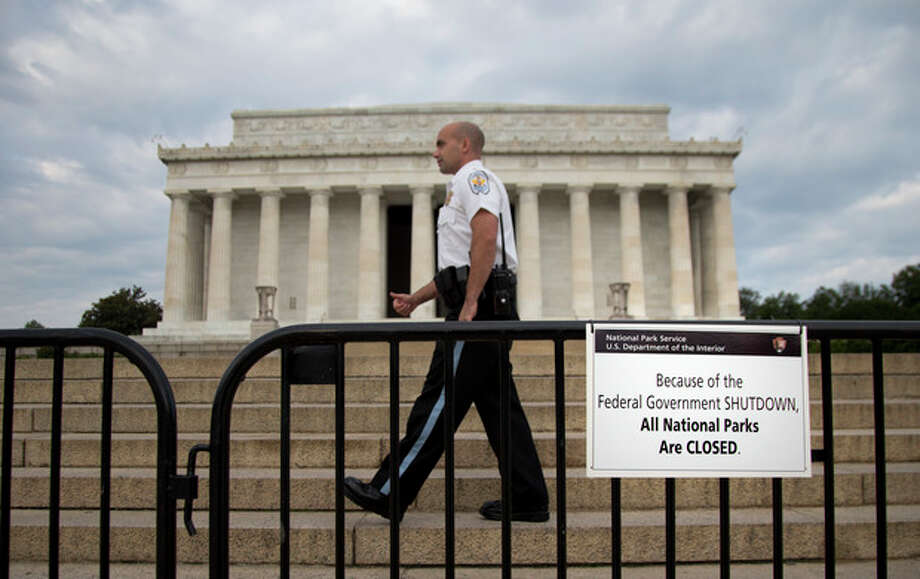 "A US Park Police officer walks behind a barricade with sign reading ""Because of the Federal Government SHUTDOWN All National Parks are Closed"" in front of the Lincoln Memorial in Washington, Tuesday, Oct. 1, 2013. Congress plunged the nation into a partial government shutdown Tuesday as a long-running dispute over President Barack Obama's health care law stalled a temporary funding bill, forcing about 800,000 federal workers off the job and suspending most non-essential federal programs and services. (AP Photo/Carolyn Kaster) / AP"