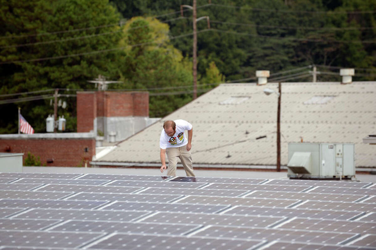 In this Thursday, Sept. 26, 2013 photo, Mike Easterwood checks one of the solar panels installed on the roof of his 1947-era building in Decatur,Ga. Easterwood paid about $320,000 to install nearly 400 solar panels on top of his self-storage business near Atlanta. (AP Photo/David Tulis)