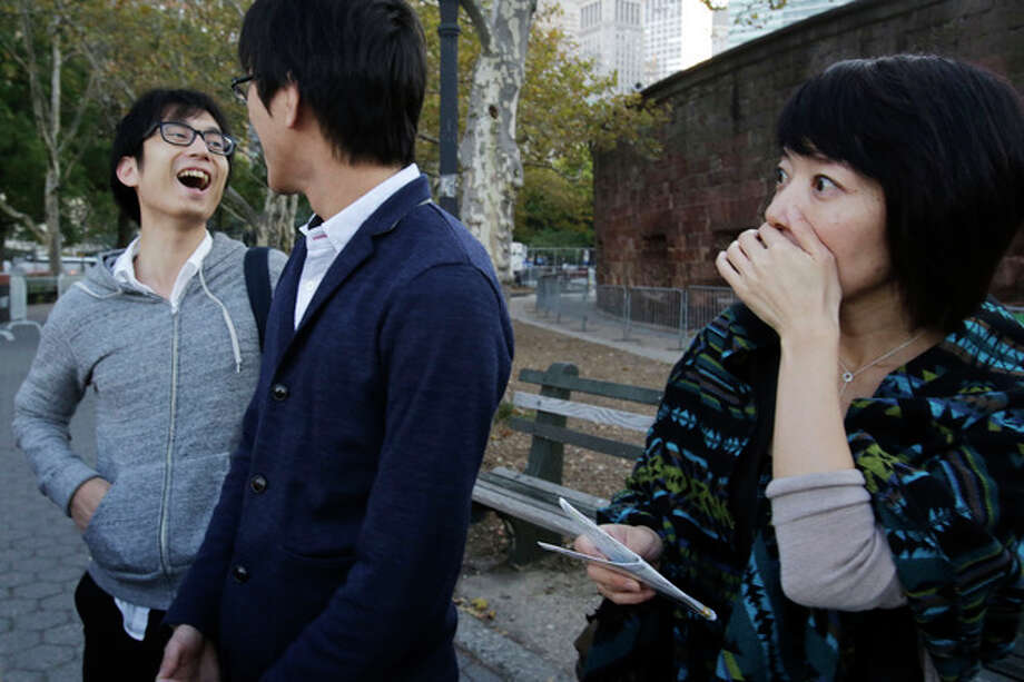 Tourist Tomoko Ida, right, of Tokyo, covers her mouth when she hears that the Statue of Liberty is closed, Tuesday, Oct. 1, 2013 in New York. Traveling with her are Jin Onuki, left, and Tomoya Osada. The shutdown, the first since the winter of 1995-96, closed national parks across the nation. (AP Photo/Mark Lennihan) / AP