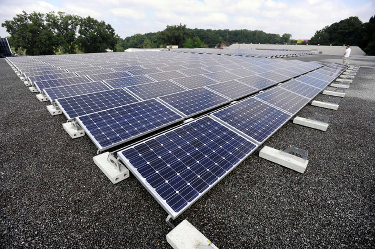 In this Thursday, Sept. 26, 2013, photo, Decatur Self Storage's array of solar cells are installed on the flat roof of the building as they capture solar energy and convert it to electrical energy for the storage facility, in in Decatur, Ga. Owner Mike Easterwood also returns excess electricity to the Georgia Power Company electrical grid in exchange for a reduced monthly power rate. (AP Photo/David Tulis)