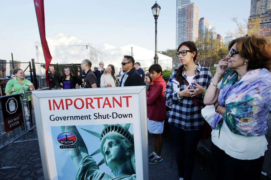 Tourists who had hoped to visit the Statue of Liberty stand near the dock used by Liberty Island ferries, Tuesday, Oct. 1, 2013 in New York. A government shutdown, the first since the winter of 1995-96, closed national parks across the nation. (AP Photo/Mark Lennihan) / AP