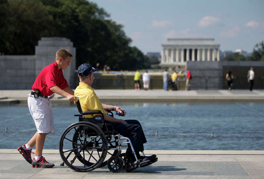 Korean War veteran Robert Olson, from Iowa, is pushed in his wheelchair by Zach Twedt, also from Iowa, around the National World War II Memorial in Washington, Tuesday, Oct. 1, 2013. Veterans who had traveled from across the country were allowed to visit the National World War II Memorial after it had been officially closed because of the partial government shutdown. After their visit, the National World War II Memorial was closed again. The Lincoln Memorial is seen in the distance. (AP Photo/Carolyn Kaster) / AP