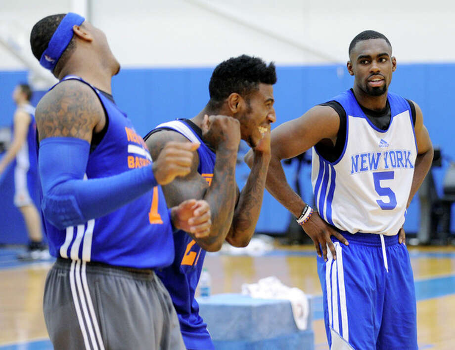 New York Knicks' Tim Hardaway, Jr. (5) looks on as Iman Shumpert and Carmelo Anthony, left, react to their shooting drill at the teams NBA basketball training camp Tuesday, Oct. 1, 2013, in Greenburgh, N.Y. (AP Photo/Bill Kostroun) / FR51951 AP