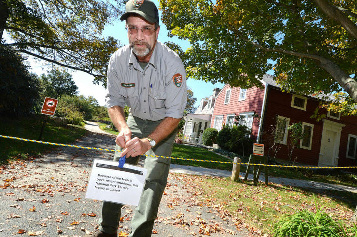Weir Farm National Historic Site Facility Manager Kevin Monthie places a sign on a rope strung accross the entrance to the Park in Wilton, stating the National Park service facility is closed due to the Federal Government shutdown on Tuesday.