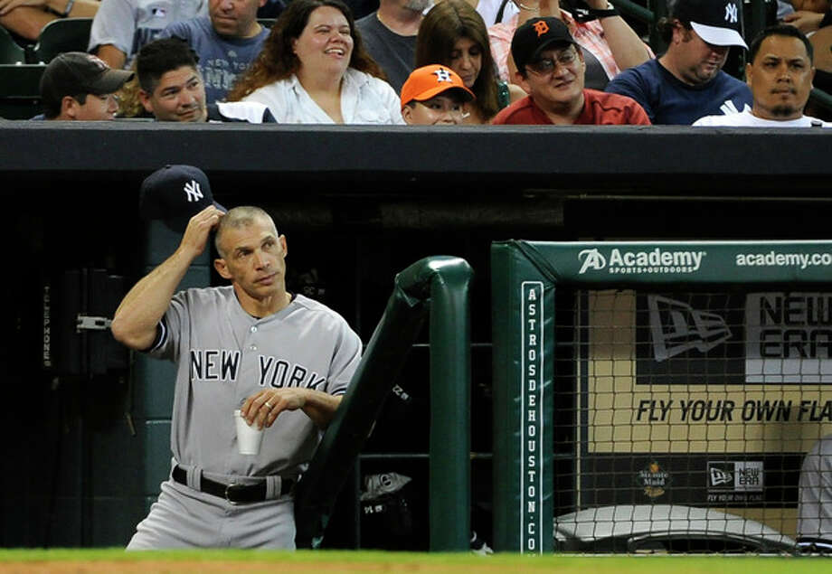New York Yankees manager Joe Girardi scratches his head as he stands in the dugout in the 13th inning of a baseball game against the Houston Astros Sunday, Sept. 29, 2013, in Houston. The Yankees won 5-1 in 14 innings. (AP Photo/Pat Sullivan) / AP