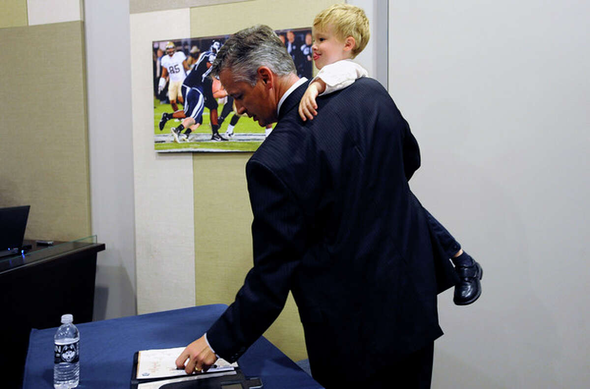 Connecticut interim head coach and former offensive coordinator T.J. Weist leaves an NCAA college football news conference while holding his son James, Monday, Sept. 30, 2013, in Storrs, Conn. Weist is taking over for fired coach Paul Pasqualoni. (AP Photo/Jessica Hill)