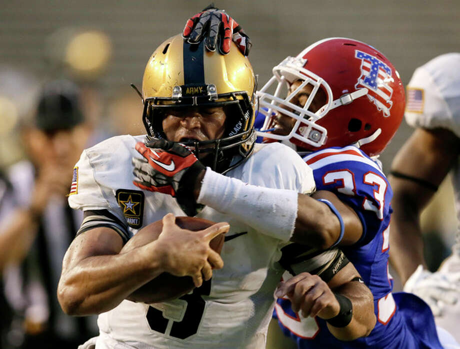 Army quarterback Angel Santiago (3) is dragged down by the helmet by Louisiana Tech safety Thomas McDonald (33) just shy of the end zone on a quarterback keeper in the second half of an NCAA college football game, Saturday, Sept. 28, 2013, in Dallas. Army won 35-16. (AP Photo/Tony Gutierrez) / AP