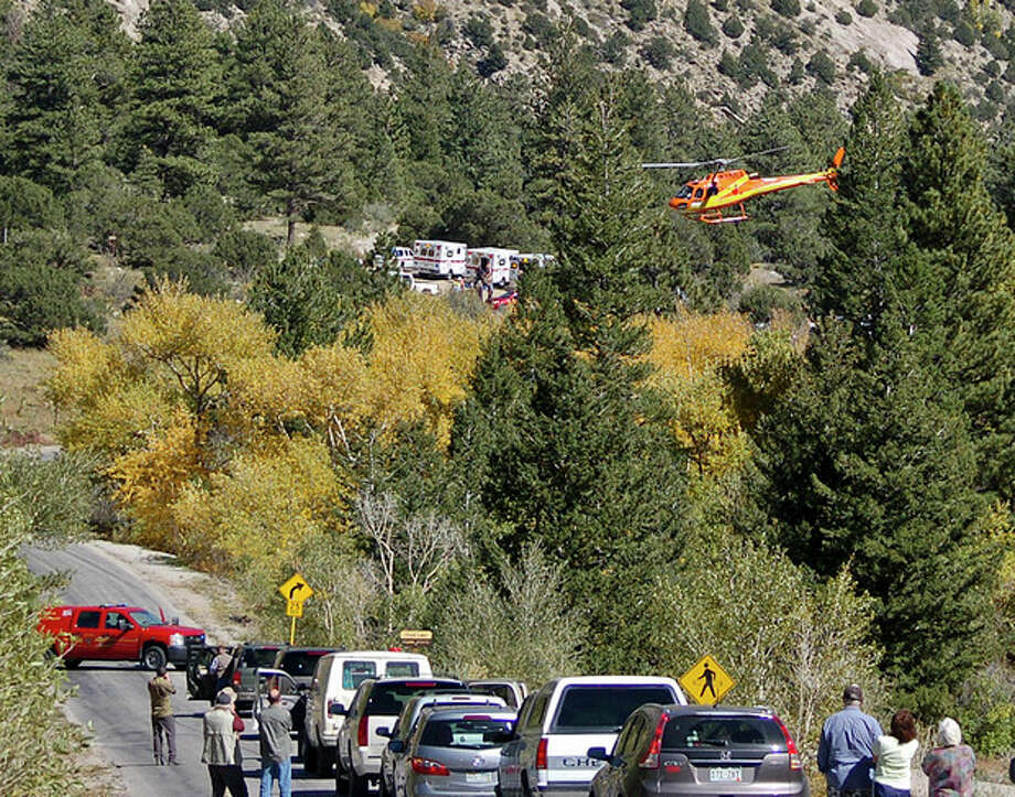A Flight for Life Helicopter rises above backed up traffic Monday Sept. 30, 2013, in south-central Colorado. Roads were closed as emergency personnel work to aid hikers trapped after a rock slide on the trail to Agnes Vaille Falls. (AP Photo/The Mountain Mail, James Redmond) / The Mountain Mail