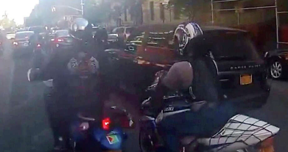 In this frame grab from video provided by the New York Police Department, motorcyclists ride alongside a sport utility vehicle, Sunday, Sept. 29, 2013, in New York. Police say that a man driving with his family along a New York City highway was attacked and beaten by a large group of motorcyclists who first surrounded his sport utility vehicle and stopped it on the road, then chased him for miles after he plowed through the blockade of bikes in an attempt to escape. (AP Photo/New York Police Department) / New York Police Department