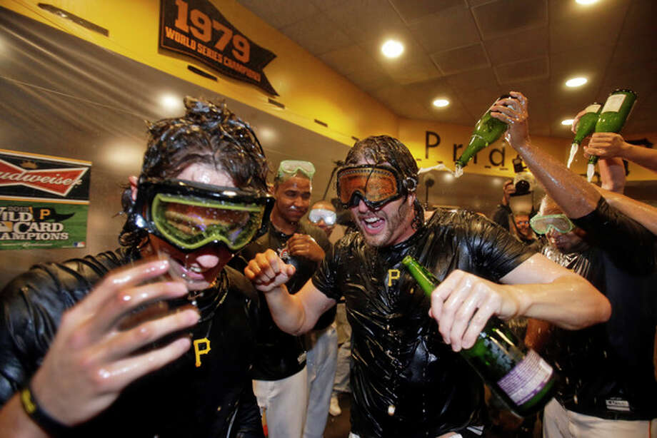 Pittsburgh Pirates' Jason Grilli, center, celebrates with Jeff Locke, left, after the Pirates defeated the Cincinnati Reds 6-2 in the NL wild-card playoff baseball game in Pittsburgh on Tuesday, Oct. 1, 2013. The Pirates advanced to the NL division series against the St. Louis Cardinals. (AP Photo/Gene J. Puskar) / AP