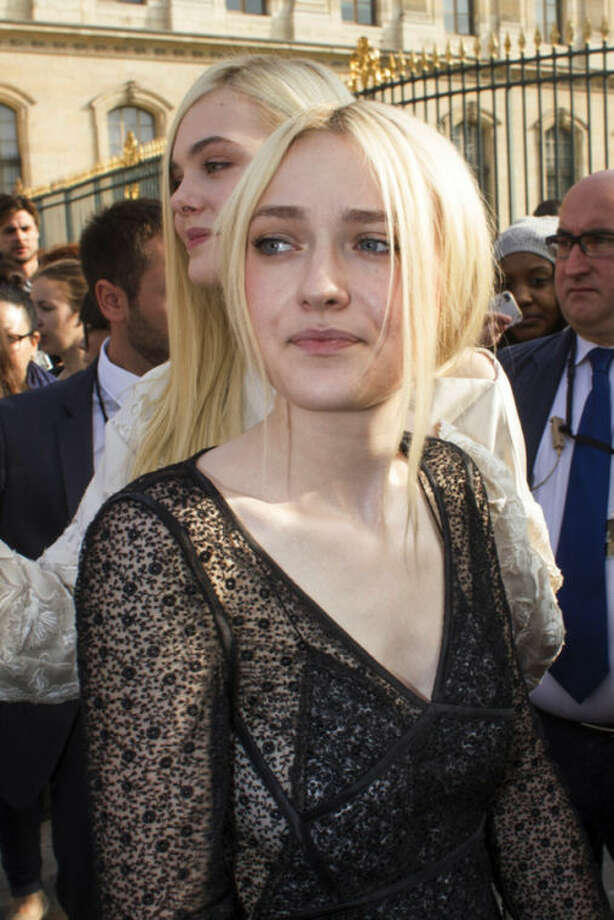 Dakota Fanning, foreground, and her sister Elle Fanning, rear, leave after attending the presentation of Vuitton's ready-to-wear Spring/Summer 2014 fashion collection, presented Wednesday, Oct. 2, 2013 in Paris. (AP Photo/Thibault Camus)