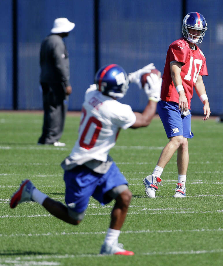 New York Giants wide receiver Victor Cruz, front, makes a catch on a pass from quarterback Eli Manning, back, during NFL football practice, Wednesday, Oct. 2, 2013, in East Rutherford, N.J. (AP Photo/Julio Cortez) / AP