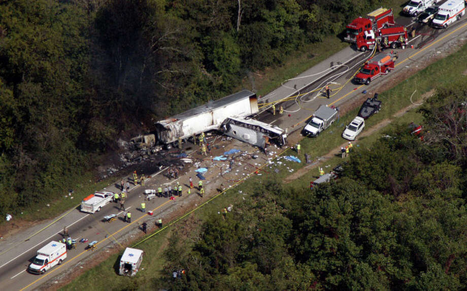 In this aerial photo, emergency workers respond to a crash involving a church bus and a tractor-trailer near Dandridge, Tenn., on Wednesday, Oct. 2, 2013. Authorities say a tire on the bus blew out and the bus hit the tractor-trailer and a sport utility vehicle, killing eight people. (AP Photo/Citizen Tribune, Gary Smith) / Citizen Tribune