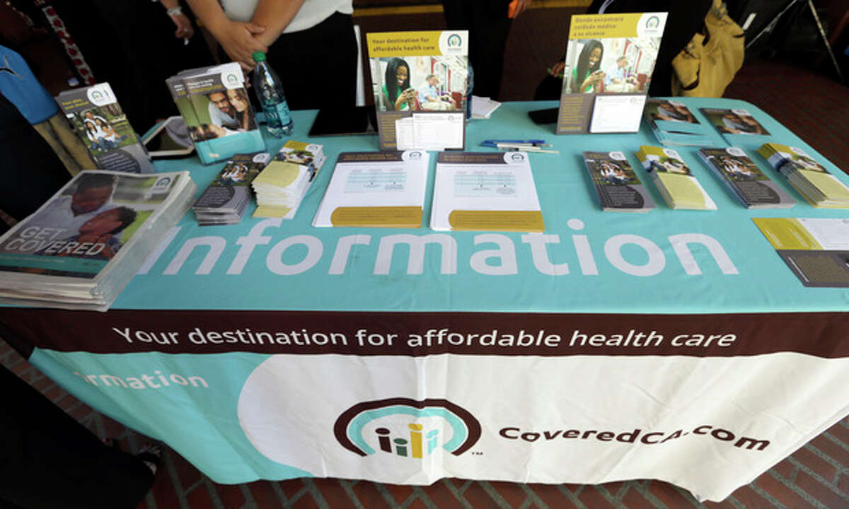 An information table is seen at Union Station in downtown Los Angeles as people seek information on state-provided health insurance, while a celebration is underway to inaugurate the first day people can enroll Tuesday, Oct. 1, 2013. Californians who buy their own health insurance and those who have been hoping for coverage began using the state's online marketplace Tuesday after it opened for business on the first day of enrollment. (AP Photo/Reed Saxon)