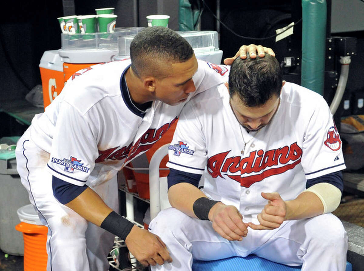 Cleveland Indians' Michael Brantley, left, consoles Jason Kipnis after the Tampa Bay Rays defeated the Indians 4-0 in the AL wild-card baseball game Wednesday, Oct. 2, 2013, in Cleveland. (AP Photo/Phil Long)