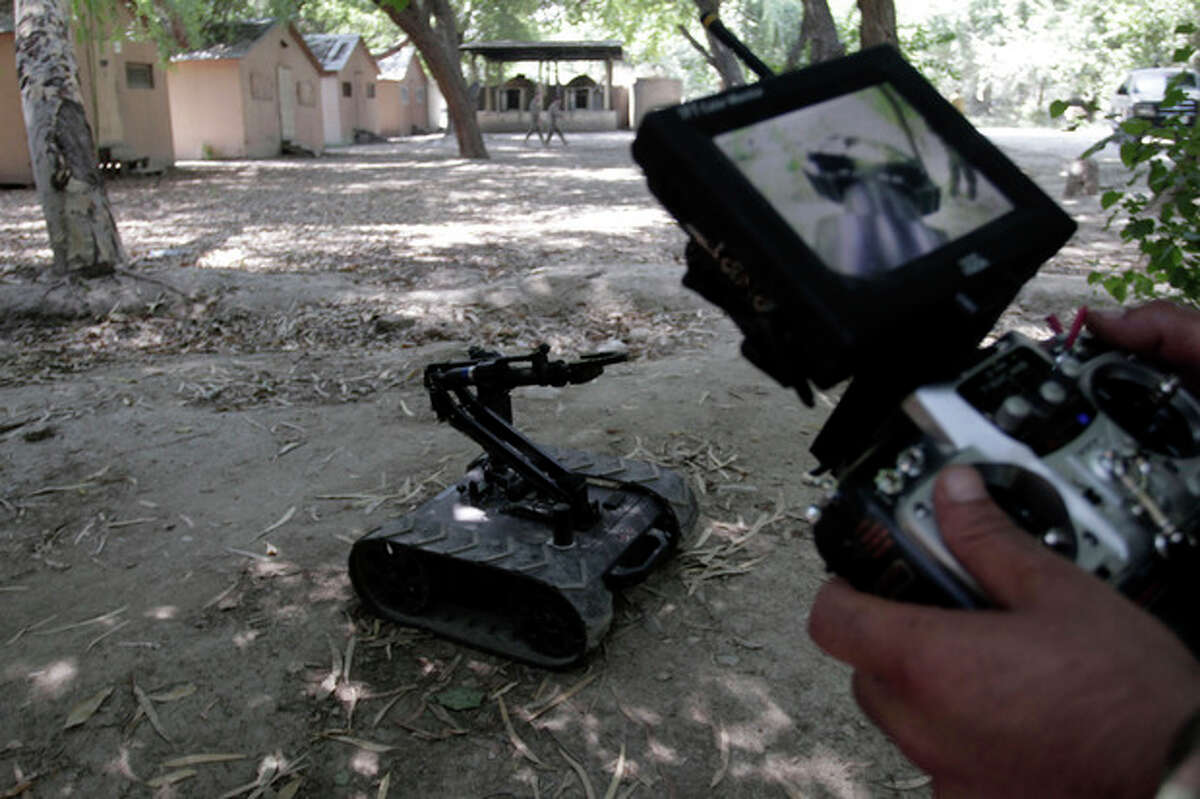In this Tuesday, Aug. 27, 2013 photo, Afghan army soldier Ali Raza, 30, uses a robotic device during an IED, or improvised explosive device, defusing training exercise in Jalalabad, east of Kabul, Afghanistan. After 12 years of war, roadside bombs are the No. 1 killer, claiming thousands of lives every year. As foreign troops wind down operations in preparation for their withdrawal at the end of 2014 insurgents are using an ever larger number of these explosives to assert their grip and recapture territory. (AP Photo/Rahmat Gul)