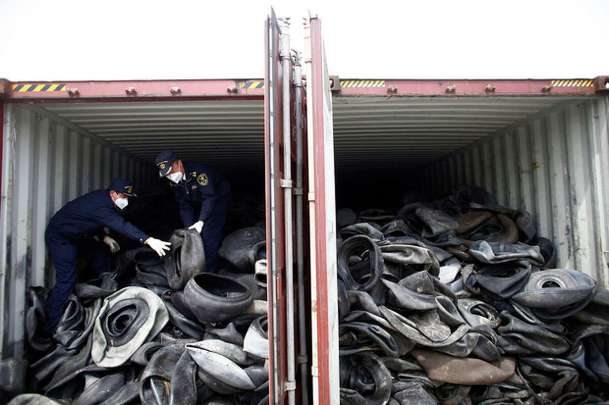 In this photo taken April 11, 2013, Chinese customs officials check a container of illegally imported used tires in Shanghai. China for years has welcomed the world?'s trash, creating a roaring business in recycling and livelihoods for tens of thousands. Now authorities are clamping down on an industry that has helped the rich West dispose of its waste but also added to the degradation of China?'s environment. (AP Photo) CHINA OUT