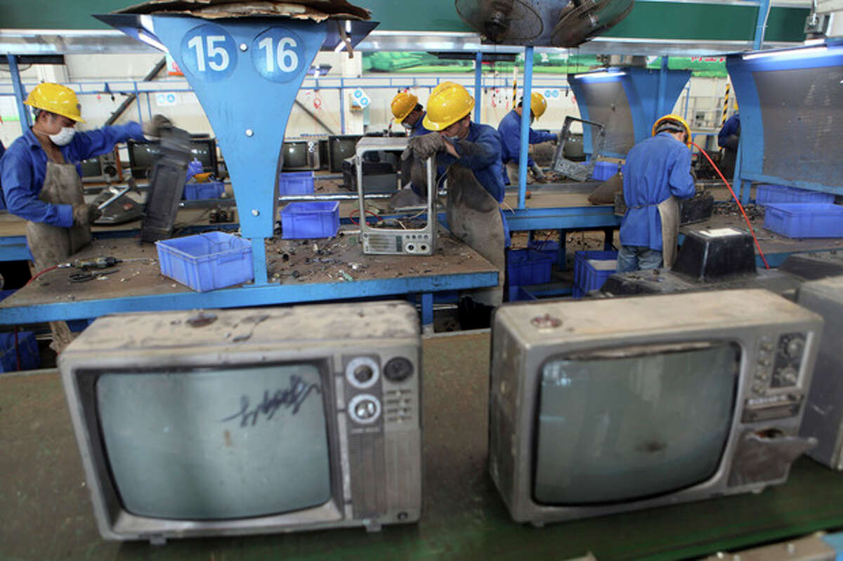 In this photo taken on Aug 28, 2013, workers dismantle television sets for recycling at a workshop in an environmental technology company in Zhuzhou in southern China's Hunan province. China?'s recycling industry has boomed over the past 20 years. Its manufacturers needed the metal, paper and plastic and Beijing was willing to tolerate the environmental cost. But environmentalists have long complained the industry is poisoning China?'s air, water and soil. (AP Photo) CHINA OUT