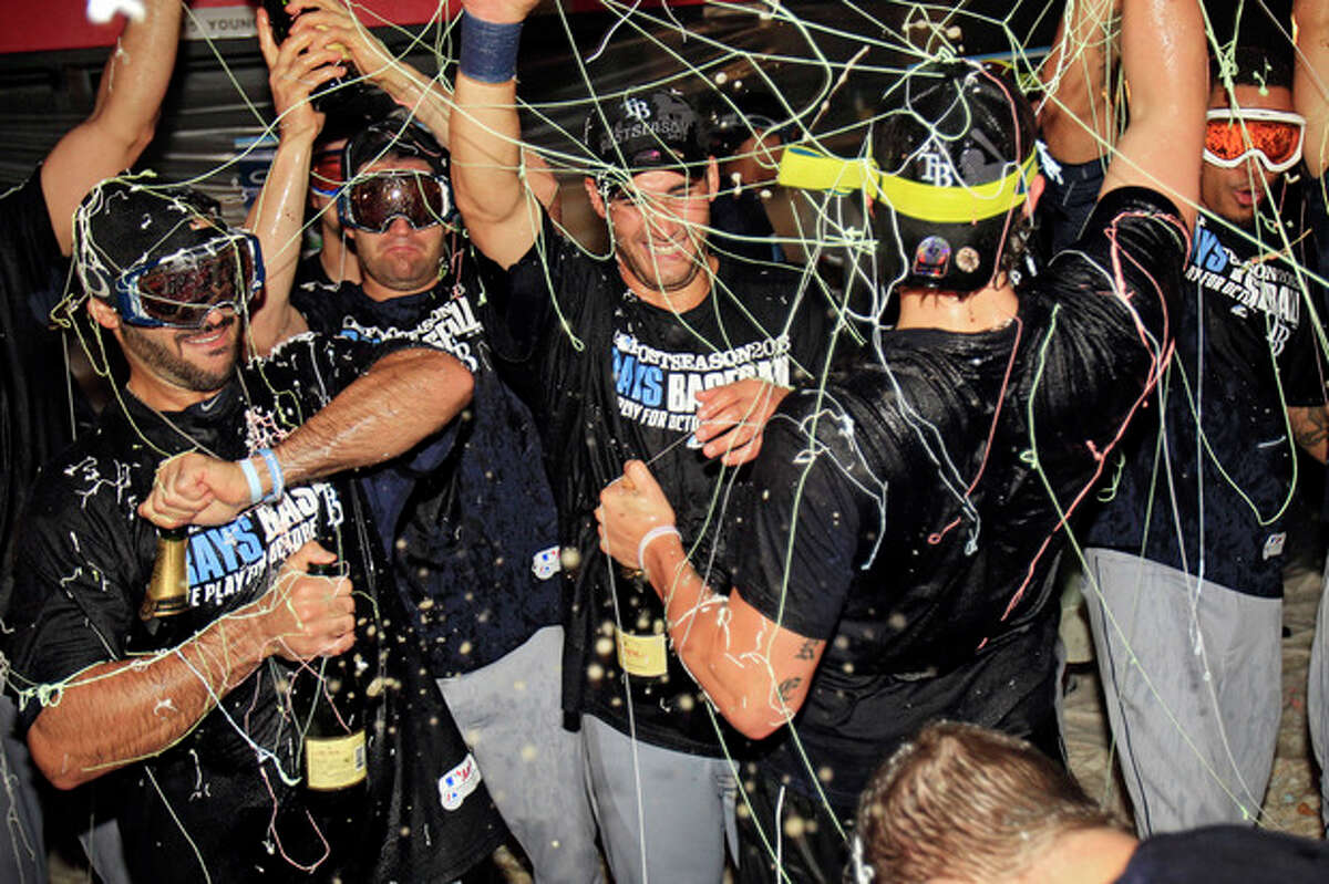 Tampa Bay Rays players celebrate in the clubhouse after beating the Cleveland Indians 4-0 in the AL wild-card baseball game Wednesday, Oct. 2, 2013, in Cleveland. The Rays advance to the AL division series against the Boston Red Sox. (AP Photo/Tony Dejak)