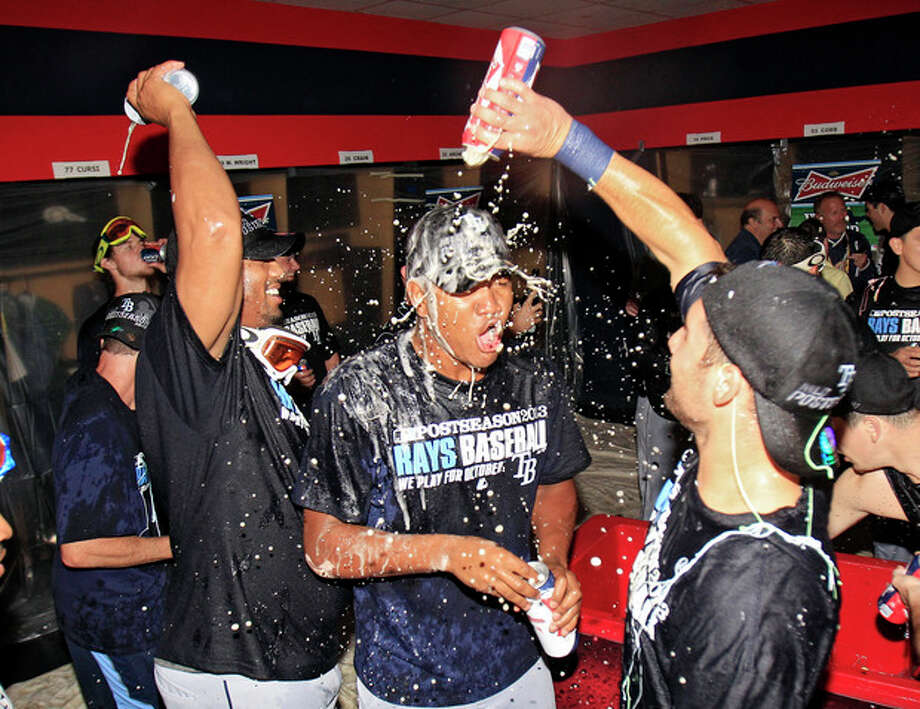 Tampa Bay Rays players celebrate in the clubhouse after beating the Cleveland Indians 4-0 in the AL wild-card baseball game Wednesday, Oct. 2, 2013, in Cleveland. The Rays advance to the AL division series against the Boston Red Sox. (AP Photo/Tony Dejak) / AP