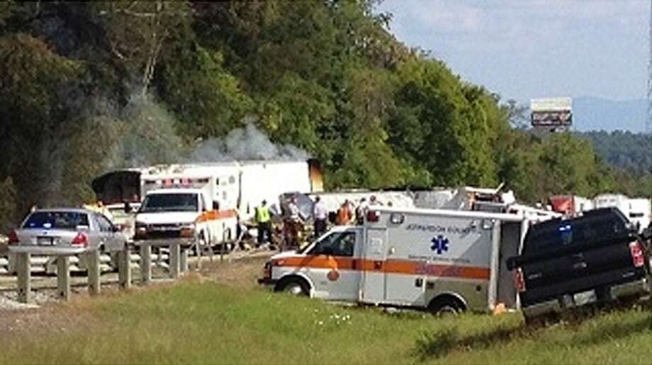 In this image released by WVLT -TV, authorities work at the scene of an interstate accident, near Dandridge, Tenn. on Wednesday, Oct. 2, 2013. A passenger bus has overturned in Jefferson County, completely blocking the eastbound lanes of Interstate 40. (AP Photo/ WVLT -TV) MANDATORY CREDIT / WVLT -TV