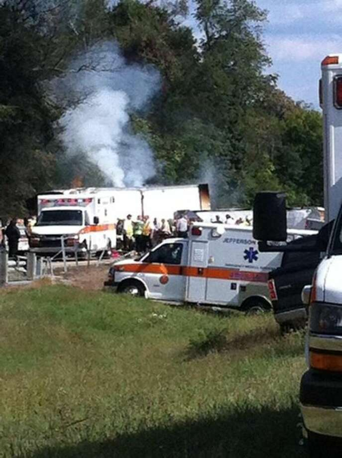 In this image released by WATE, authorities work at the scene of an interstate accident, near Dandridge, Tenn. on Wednesday, Oct. 2, 2013. A passenger bus has overturned in Jefferson County, completely blocking the eastbound lanes of Interstate 40. (AP Photo/ WATE, Stephanie Beecken)