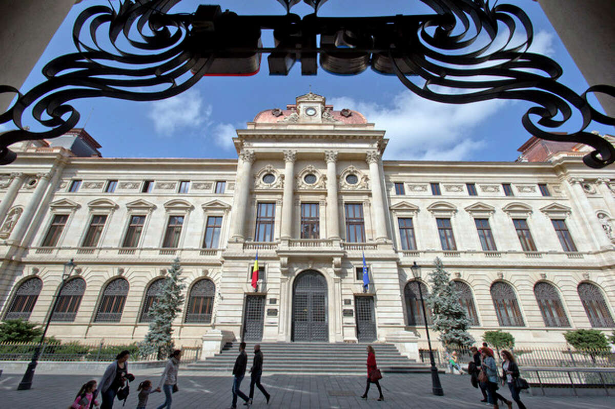 FILE - This April 10, 2013 file photo shows people walking by the National Bank of Romania in the old part of Bucharest, the Romanian capital. (AP Photo/Vadim Ghirda, File)