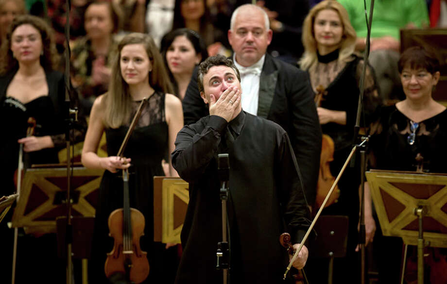 This Sept. 24, 2013 photo shows Russian-born violinist Maxim Vengerov reacting during a round of applause at the Romanian Athenaeum concert hall in Bucharest, Romania, during the George Enescu classical music festival. The festival which began in 1958 is named after Romanian composer, violinist and conductor George Enescu, who lived in Romania but moved to Paris when the communists came to power. (AP Photo/Vadim Ghirda) / AP