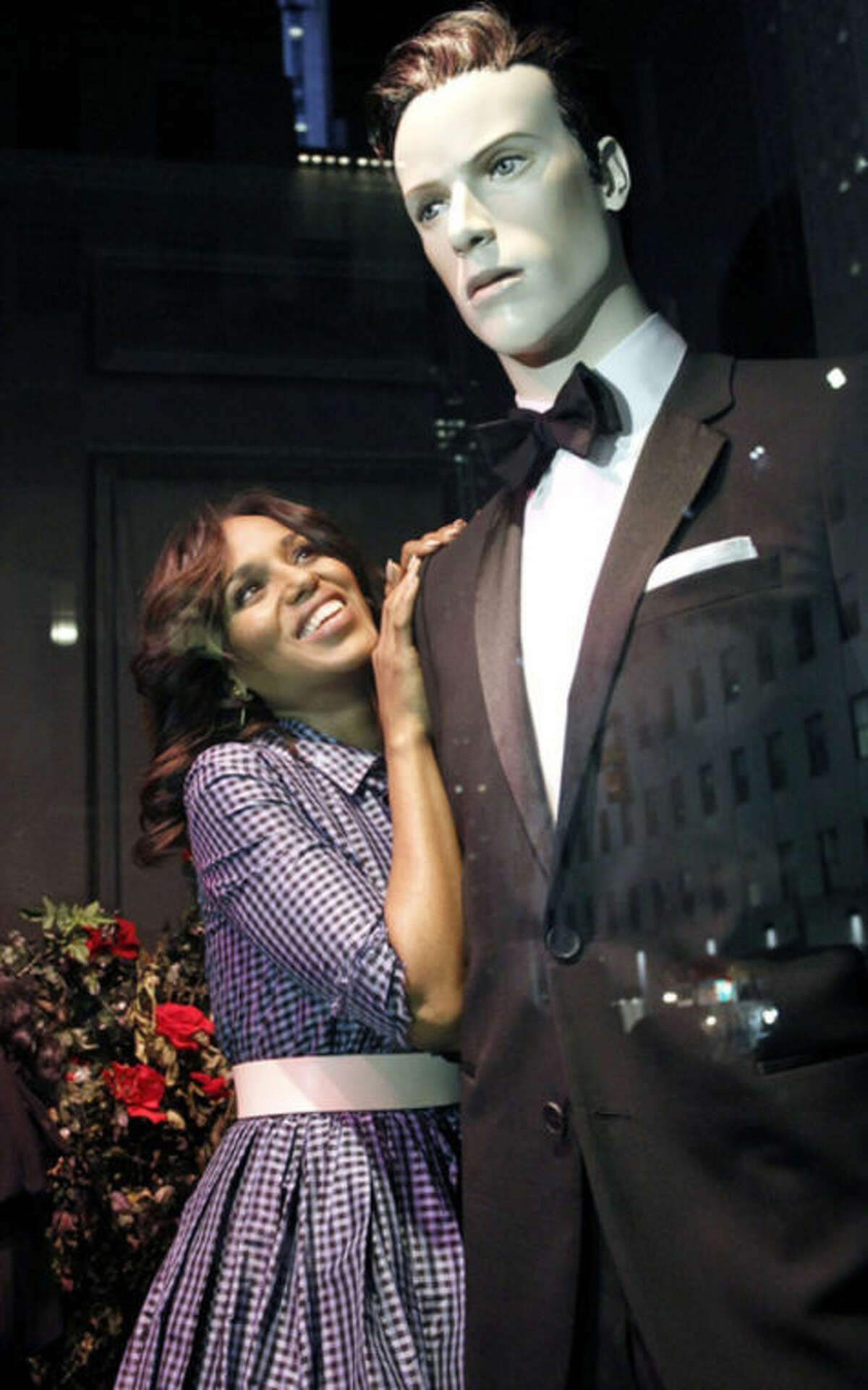"""AP Photo/ABC, Lou Rocco This photo shows actress Kerry Washington posing next to a mannequin in a tuxedo, part of an installation honoring the TV series """"Scandal"""" at Saks 5th Avenue in New York."""