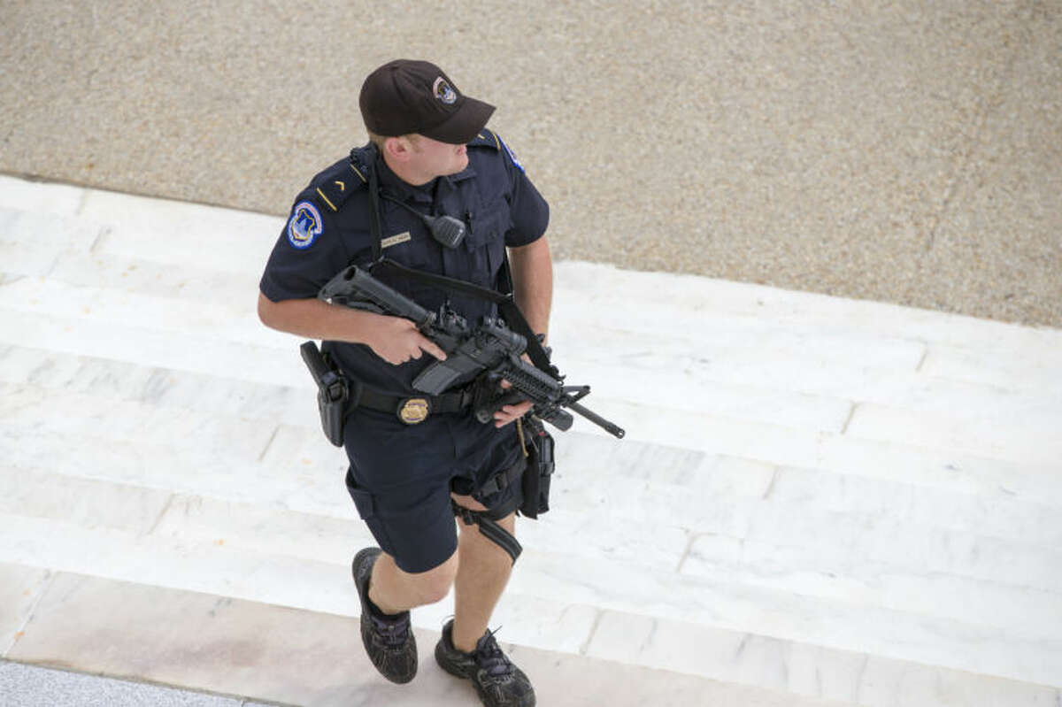 A U.S. Capitol Police officer keeps watch on the steps of the Russell Senate Office Building on Capitol Hill near the Supreme Court in Washington, Thursday, Oct. 3, 2013, after a report of shots fired. A police officer was reported injured after gunshots at the U.S. Capitol, police said Thursday. They locked down the entire complex, at least temporarily derailing debate over how to end a government shutdown. (AP Photo/J. Scott Applewhite)
