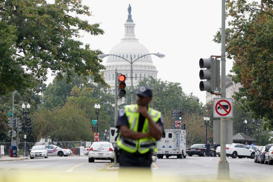 A Washington police officer stands guard on Capitol Hill in Washington, Thursday, Oct. 3, 2013, after a report of a shooting. A police officer was reported injured after gunshots at the U.S. Capitol, police said Thursday. They locked down the entire complex, at least temporarily derailing debate over how to end a government shutdown. (AP Photo/Molly Riley)