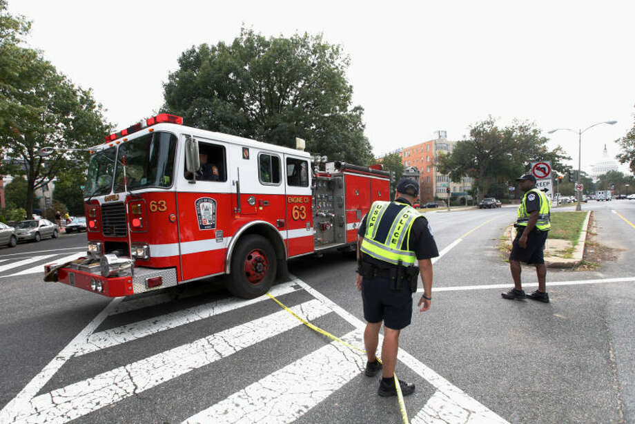 A fire truck leaves the scene of a shooting on Capitol Hill in Washington, Thursday, Oct. 3, 2013. A police officer was reported injured after gunshots at the U.S. Capitol, police said Thursday. They locked down the entire complex, at least temporarily derailing debate over how to end a government shutdown. (AP Photo/Molly Riley)