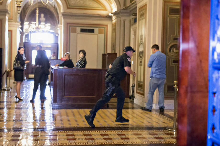 A Capitol Police officer runs through the first floor of the Senate on Capitol Hill in Washington, Thursday, Oct. 3,2013, during the lockdown order following a shooting on Constitution Avenue on Capitol Hll and near the Supreme Court. A police officer was reported injured after gunshots at the U.S. Capitol, police said Thursday. They locked down the entire complex, at least temporarily derailing debate over how to end a government shutdown. (AP Photo/J. Scott Applewhite)