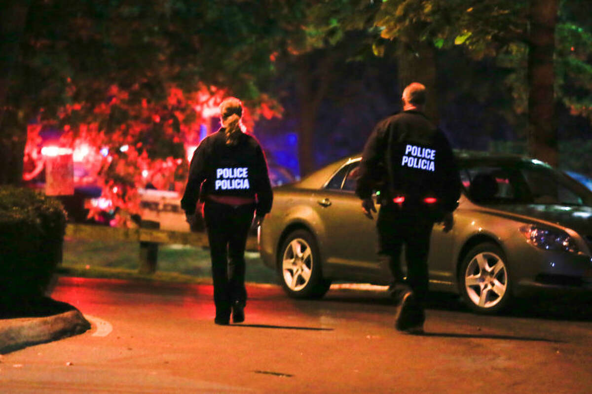 Stamford Police enter the evacuated Woodside Green condominiums thought to be the home of a woman killed by police in Washington, DC Thursday evening. Hour Photo / Chris Palermo