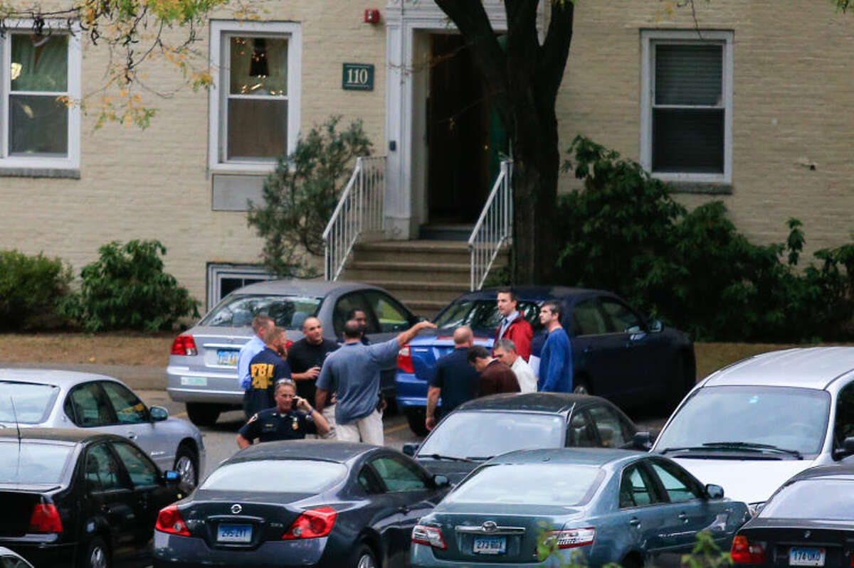 FBI and Stamford police meet outside the Woodside Green condominiums thought to be the home of a woman killed by police in Washington, DC Thursday evening. Hour Photo / Chris Palermo