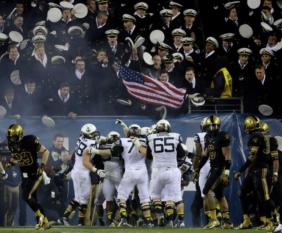 FILE - In this Dec. 8, 2012 file photo, Navy players celebrate after a touchdown during the second half of an NCAA college football game against Army in Philadelphia. The Defense Department says it has temporarily suspended all sports competitions at the service academies as a result of the partial government shutdown. The decision jeopardizes this weekend's football games _ Air Force at Navy and Army at Boston College. (AP Photo/Matt Slocum, File) / AP