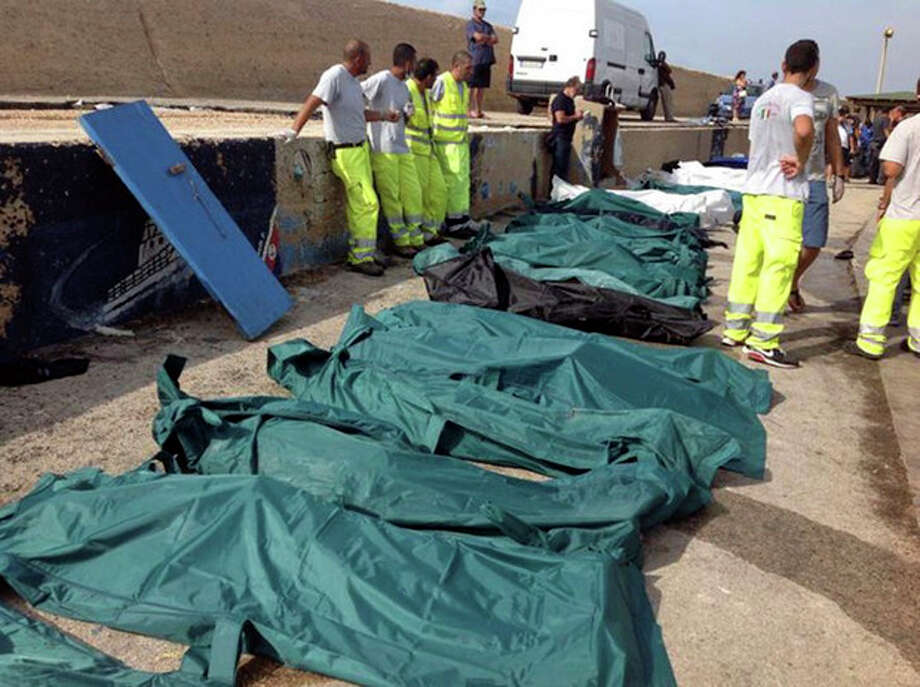 Bodies of drowned migrants are lined up in the port of Lampedusa Thursday, Oct. 3, 2013. A ship carrying African migrants to Europe caught fire and capsized off the Italian island of Lampedusa on Thursday, killing at least 94 people as it spilled hundreds of passengers into the sea, officials said. Over 150 people were rescued but some 200 others were still unaccounted for. It was one of the deadliest recent accidents in the notoriously perilous Mediterranean Sea crossing from Africa for migrants seeking a new life in the European Union. (AP Photo/Nino Randazzo, Health Care Service, HO) / Health Care Service